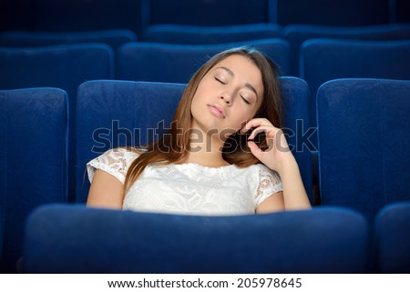 Watching is not interesting movie. Young women sleeping, watching movie at the cinema - stock photo