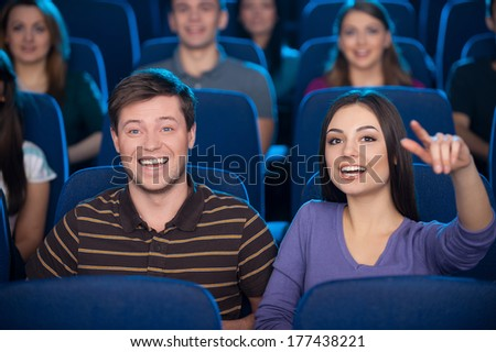 Watching movie together. Happy young couple eating popcorn and drinking soda while watching movie at the cinema  - stock photo