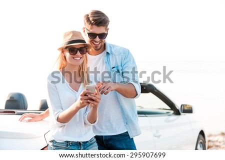 Watching photos of their road trip. Happy young couple looking at mobile phone while leaning at their white convertible - stock photo