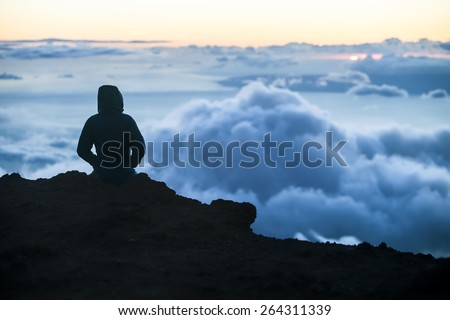 Watching sunset above Maui clouds from Haleakala - stock photo