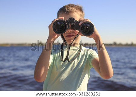 watching through binoculars. Boy looks through binoculars at the river, the position of a full-face - stock photo