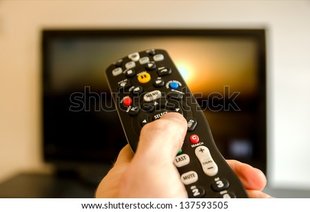 Watching tv and using remote control - stock photo