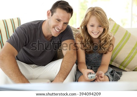 Watching TV with Dad - Father and daughter watching television together - stock photo