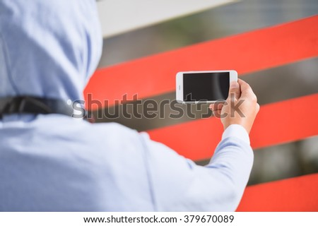 Watching video, taking selfy photo. Backview of man with headphones holding mobile smart phone on outdoors background.  - stock photo