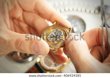 Watchmaker hands repairing mechanism of old watch closeup - stock photo