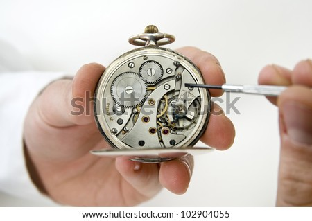 Watchmaker holding antique pocket watch show the clockwork mechanism and repair with screwdriver. - stock photo