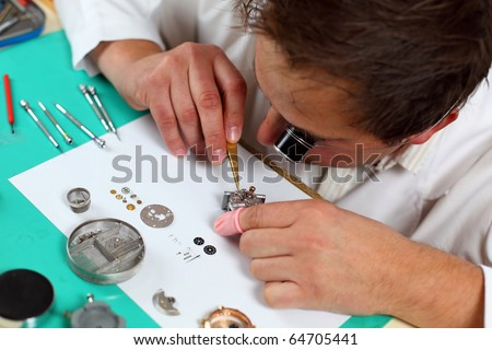 Watchmaker in his workshop repairing a wrist watch. Intentional shallow depth of field. - stock photo