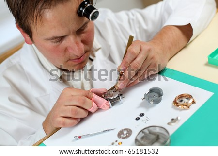 Watchmaker in his workshop repairing a wrist watch. Intentional shallow depth of field, focus on the eye. - stock photo