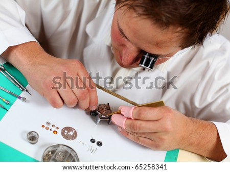 Watchmaker in his workshop repairing a wrist watch. Intentional shallow depth of field, focus on the movement. - stock photo
