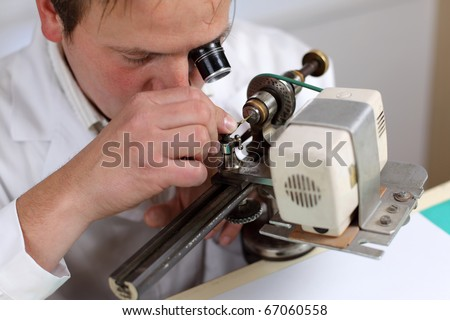Watchmaker in workshop repairing a wrist watch. Intentional shallow depth of field, focus on the eye. - stock photo