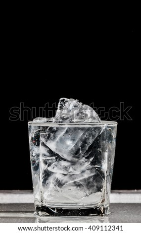 water and ice in glass on black background
