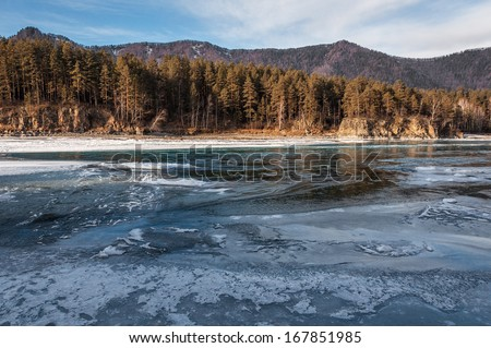 Water and ice on the turquoise river in the mountains in winter on a sunny day