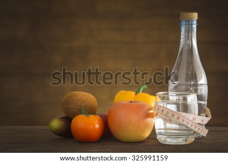 water and measuring tape with fruit on  wooden floor. Health lifestyle and fitness concept - stock photo