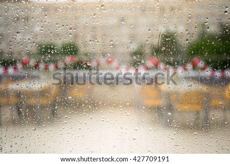 Water and rain drops on the glass, abstract view on an empty cafeteria and building - stock photo