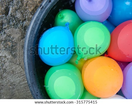 water balloons in a bucket with water - stock photo