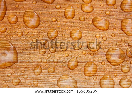 Water beads up on beautiful freshly sealed cedar wood decking after a morning rainstorm at the cottage. - stock photo