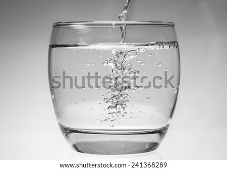 Water being poured into a glass creating bubbles - stock photo