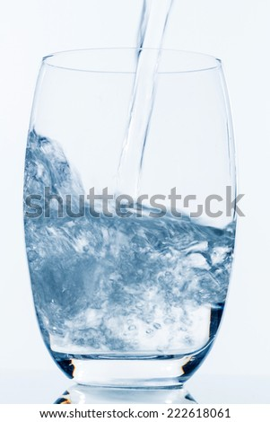 water being poured into a glass, symbol photo for drinking water, freshness, demand and consumption - stock photo