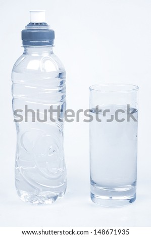 Water bottle and glass on grey background  - stock photo
