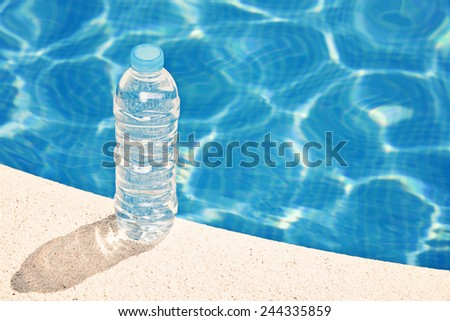 Water bottle by swimming pool - stock photo