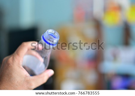 water bottle in hand blurred background.