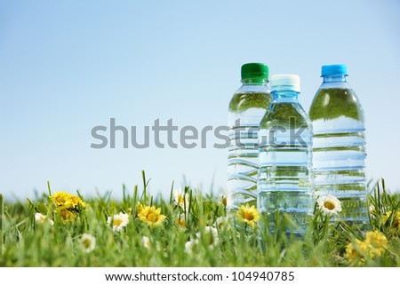 Water bottles on green grass with copy space. - stock photo