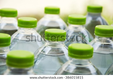 Water bottles with caps made of green plastic. - stock photo