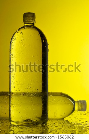 Water bottles with yellow background - stock photo