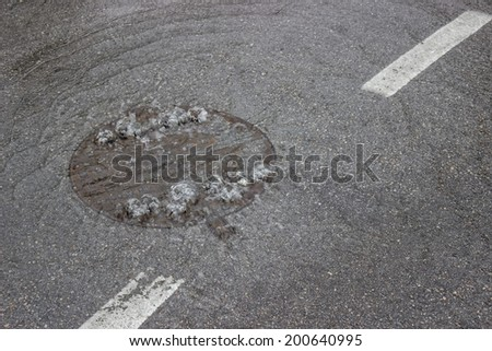 Water bubbling up through manhole cover and sewer, drain is clogged  - stock photo
