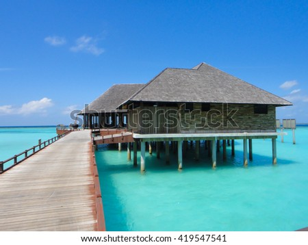 Water bungalows and wooden jetty on Maldives  - stock photo