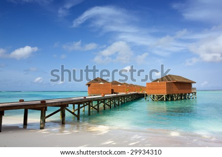 water bungalows over the ocean with jetty - stock photo