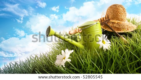 Water can and straw hat laying in grass - stock photo