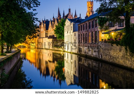 Water canal, medieval houses and bell tower at night, Bruges - stock photo