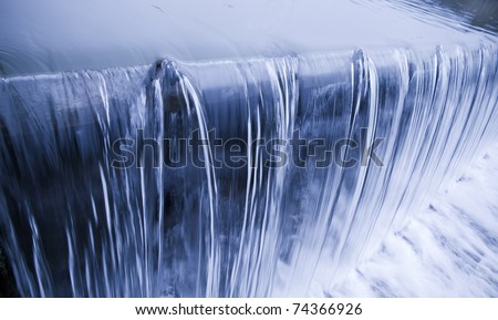 water cascade streaming down a lasher, cool white balance, concept for water saving, conservation, keeping water clean - stock photo