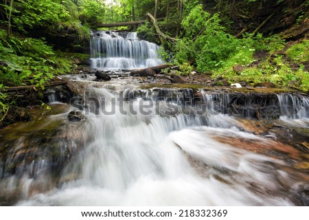 Water cascades and tumbles over a rocky stream bed at Wagner Falls in Munising Michigan. This area is very close to Pictured Rocks National Lakshore in the Upper Peninsula of Michigan - stock photo