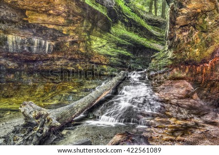 Water cascades over colorful sandstone from a narrow passage with green rocky walls In Indiana's Turkey Run State Park. - stock photo
