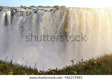 Water cascades over Victoria Falls, one of the Seven Natural Wonders of the World in Zambia, Africa, with added lens flare effect. - stock photo
