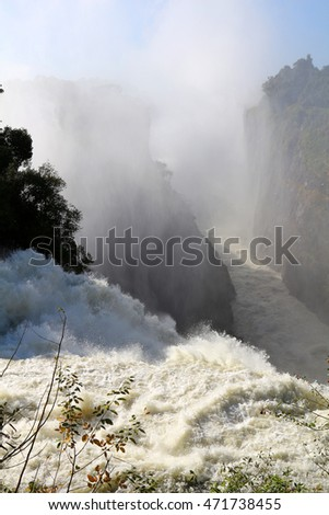 Water cascades over Victoria Falls, one of the Seven Natural Wonders of the World in Zambia, Africa.