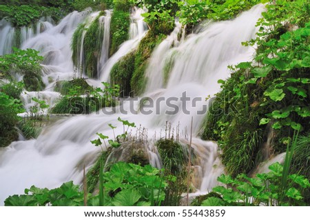 Water cascades surrounded of grass and leaves - stock photo