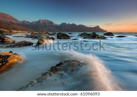 Water collides with coastal rocks as the sun sets over Kogel Bay in the Cape Province, South Africa - stock photo