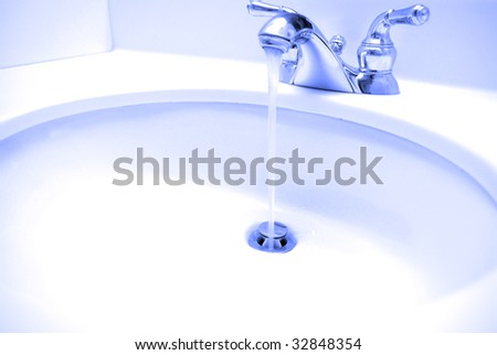 Water coming out of spout in bathroom sink and going down the drain - stock photo