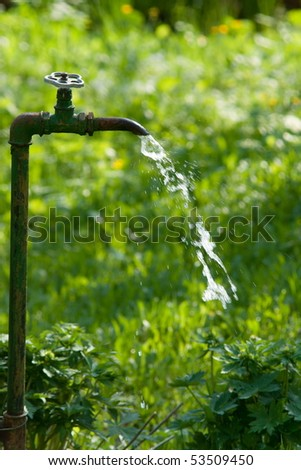 water crane in garden with flowing water - stock photo