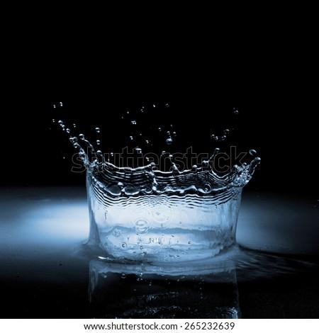 Water crown splash in black - stock photo