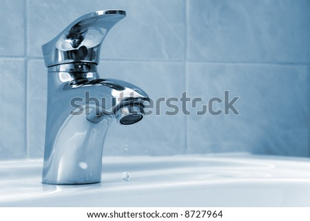 Water dripping from a faucet, blue tint - stock photo