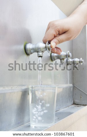 Water dripping from a faucet into a glass - stock photo