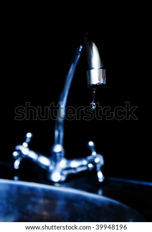 Water dripping from water faucet, closeup - stock photo