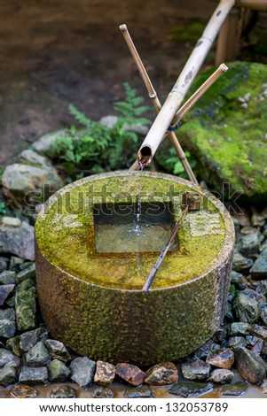 Water drips out of a delicately balanced ancient stone fountain at Ryoanji in Kyoto, Japan - stock photo