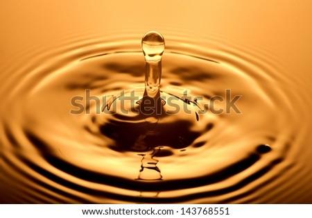 Water drop close up, orange background - stock photo