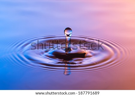 Water drop close up with concentric ripples on colourful blue and amber surface - stock photo
