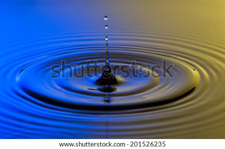 Water drop close up with concentric ripples on colourful blue and yellow surface